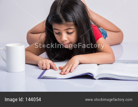 Indian school girl studying or reading book