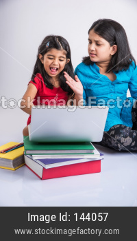 Indian girls or sisters studying with laptop and books