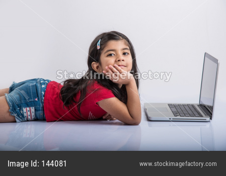 Indian school girl studying with laptop on floor