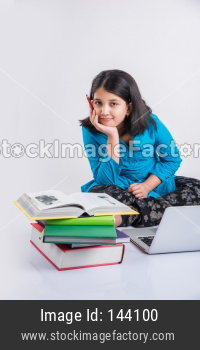 Indian school girl studying with laptop and books