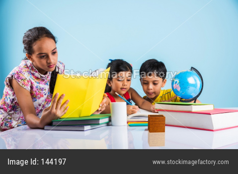 Indian school kids/siblings studying at home with books