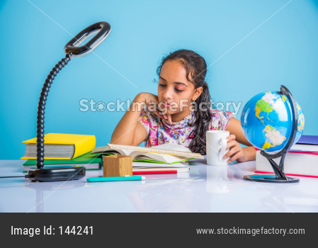 Indian school girl studying at home with books