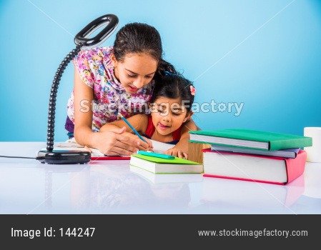 Indian school kids/sisters/siblings studying at home with books