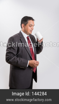 Indian handsome Businessman having coffee / tea / hot drink