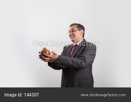 successful Indian handsome Businessman showing a piggy bank
