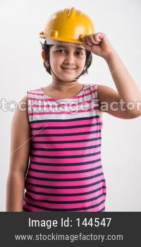 Indian small girl want to be an architect / engineer, wearing Yellow Hard Hat and holding paper drawing Roll