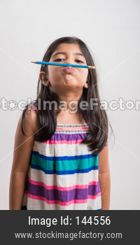Naughty little indian girl holding a pencil like a mustache.  standing isolated over white background