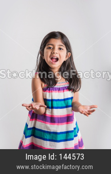 Small indian girl standing and looking up with hands stretched, catching something