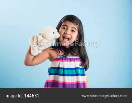 cute little indian girl playing with white soft toy puppet with happy expressions. Standing against sky blue background