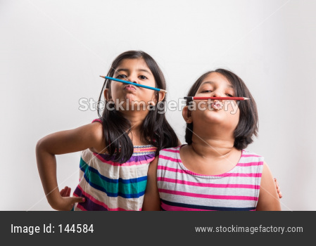 two Naughty little indian girls holding a pencil like a mustache.  standing isolated over white background