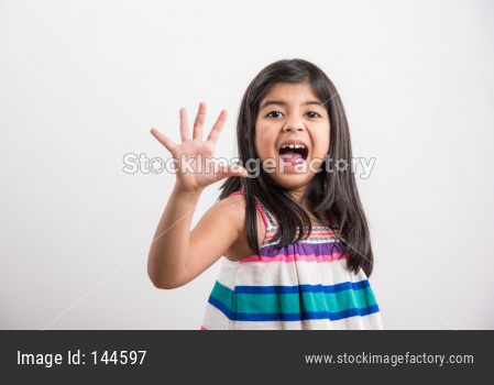 Indian small girl showing numbers with fingers over white background