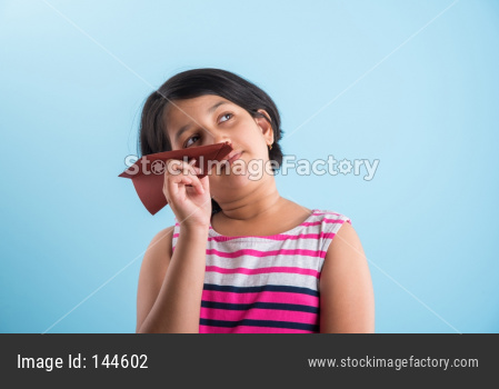 Cute little Indian girl flying a handmade paper aeroplane, isolated over blue or white background