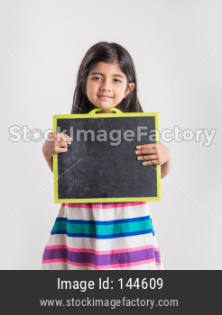Cute little Indian girl holding and presenting blank school slate board, isolated over white background