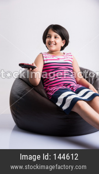 Indian small girl watching Television / TV while holding remote control, sitting over bean bag