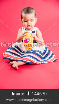 Small Indian Infant playing with colourful toys
