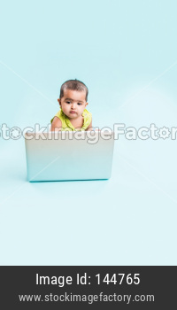 Small Indian Infant using laptop computer