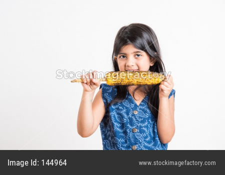 Cute little indian girl eating Grilled Corn or Bhutta, Standing isolated over white background