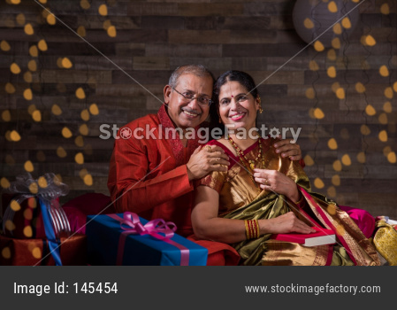 Indian senior couple in traditional wear opening gift boxes on anniversary or Diwali festival