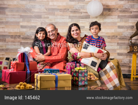 Indian family celebrating diwali with gifts and sweets