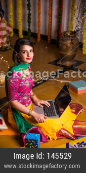 Young girl online shopping using laptop computer on festival night