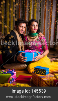 Indian young couple sitting close on diwali / anniversary