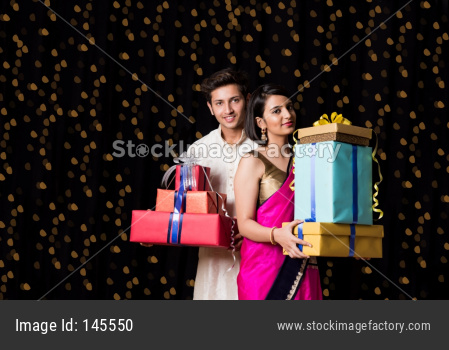 Indian young couple holding gift boxes