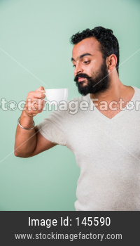 Indian Bearded young man drinking tea / coffee