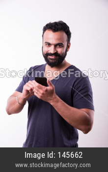 Indian Bearded young man calling or using smartphone