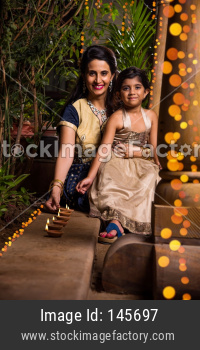 Indian mother and daughter celebrating diwali festival