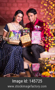 Indian couple celebrating Diwali festival / anniversary or birthday with gifts and sweets