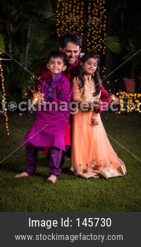 Indian young father with kids celebrating diwali festival