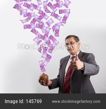 Indian businessman with New currency note of rs 2000 falling in piggy bank