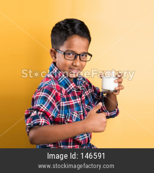 Small boy drinking plain milk in a glass