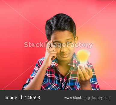 Small boy holding glowing light bulb with surprised expressions