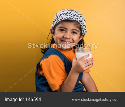 Small girl drinking plain milk in a glass before going to school