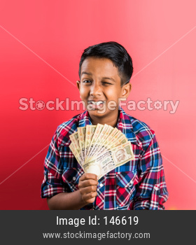 Kid/boy holding indian Currency note fan