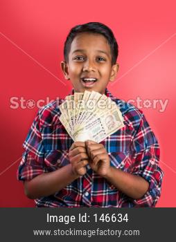 Kid/boy holding indian Currency note fan