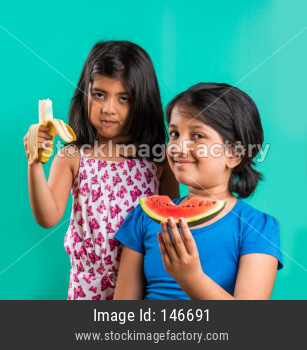 Small girl eating banana/kela and watermelon/tarbuj