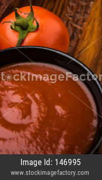 Farm Fresh Red Tomato with paste or puree in a ceramic bowl. Selective focus