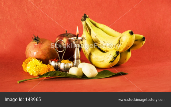 Hindu Puja elements arranged over colourful background included fruits, sweers and diya
