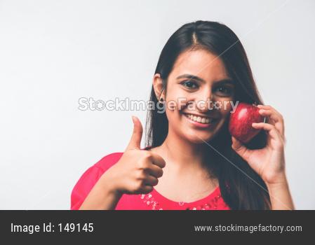 Young beautiful girl eating fresh fruit