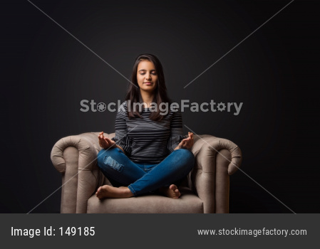 Pretty young girl meditating on sofa/couch