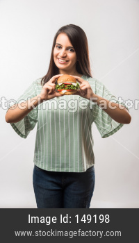Beautiful young girl eating burger