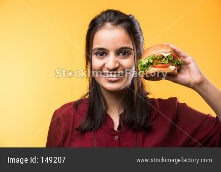 Beautiful young girl eating burger
