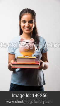 Young beautiful female student holding piggy bank with books