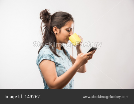 Indian girl using smartphone while drinking coffee
