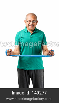 Senior indian man doing weight training / gym