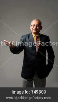 Senior indian/asian businessman or executive with hands folded or presenting something over grey background