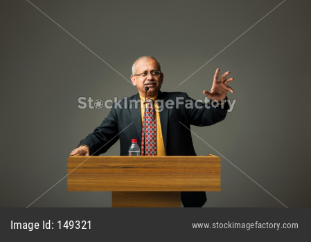Happy Indian/asian handsome senior businessman speaking with mic at podium in office or auditorium presenting something