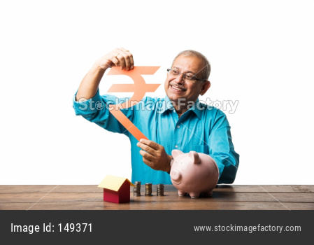 senior Indian/asian man and savings concept - with piggy bank, currency notes, 3d house model, money fan, pile of coins. sitting